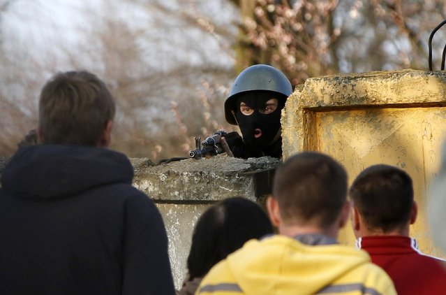"""An Ukrainian soldier aims his rifle at pro-Russia protesters gathered in front of a Ukrainian airbase in Kramatorsk, in eastern Ukraine April 15, 2014. Ukrainian armed forces on Tuesday launched a """"special operation"""" against militiamen in the country's Russian speaking east, authorities said, recapturing a military airfield from pro-Moscow separatists. (Photo by Marko Djurica/Reuters)"""