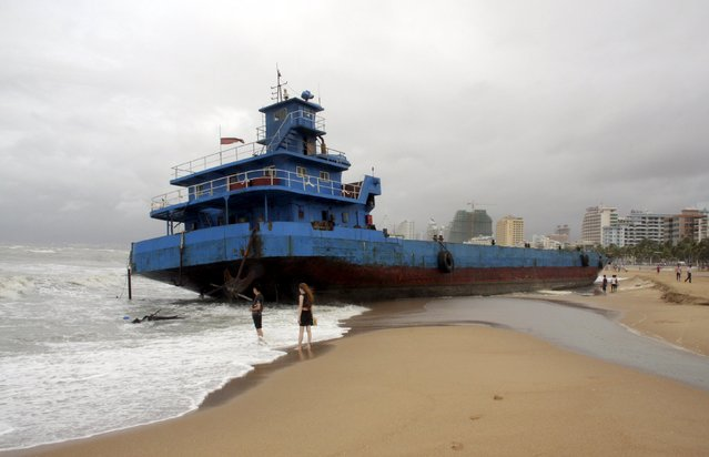 People stand on a beach next to a stranded boat which was pushed ashore by waves under the influence of typhoon Kujira, in Sanya, Hainan province, China, June 23, 2015. China's National Meteorological Center remained on blue alert for typhoon Kujira on Wednesday morning, after the eighth typhoon of this year made landfall in south China's Hainan province on Monday, Xinhua News Agency reported. (Photo by Reuters/Stringer)