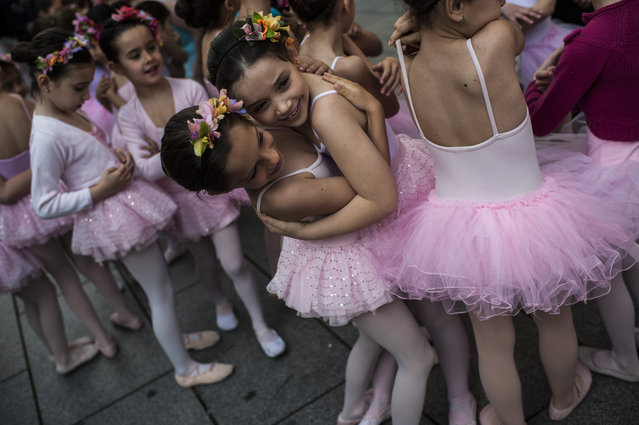 A group of young classic dancers are seen prior to performing on the street during the Dance Day, in Pamplona northern Spain, Saturday, April 12, 2014. (Photo by Alvaro Barrientos/AP Photo)