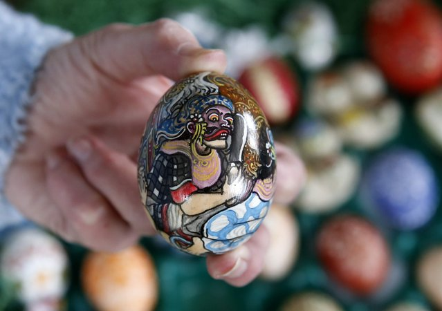 German pensioner Christa Kraft displays a colourful hand-painted Easter egg before she decorates an apple tree in the garden of her summerhouse, in the eastern German town of Saalfeld, March 19, 2014. (Photo by Fabrizio Bensch/Reuters)