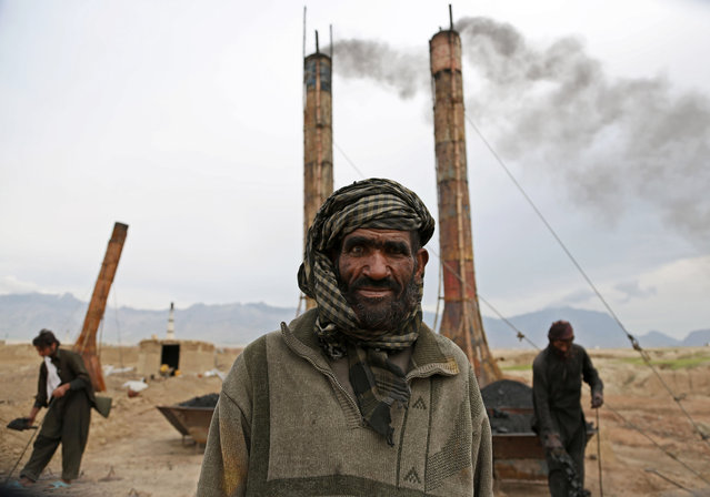 Mohammad Malook 55, poses for a photograph as he works at a brick factory on the outskirts of Kabul, Afghanistan, Monday, April 21, 2014. Men generally work for 8 hours a day, six days a week, and make about 350 Afghani ($6) per day. (Photo by Rahmat Gul/AP Photo)