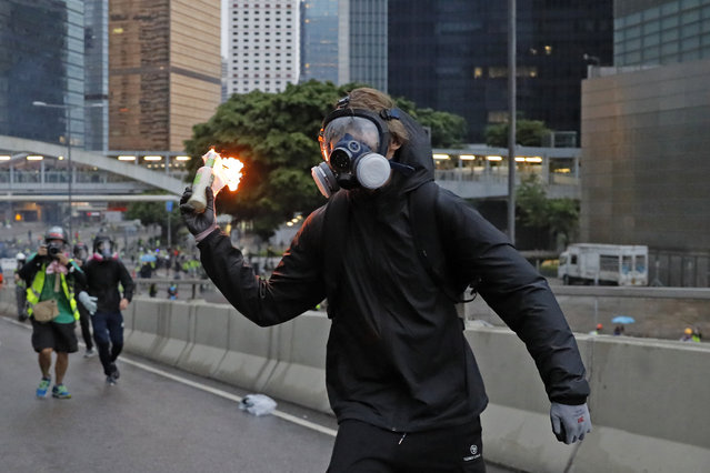 A protestor prepares to throw a molotov cocktail toward police officers in Hong Kong, Saturday, August 31, 2019. Many of the protesters outside Hong Kong government headquarters have retreated as large contingents of police arrive on the streets in what looks like preparation for a clearing operation. (Photo by Kin Cheung/AP Photo)