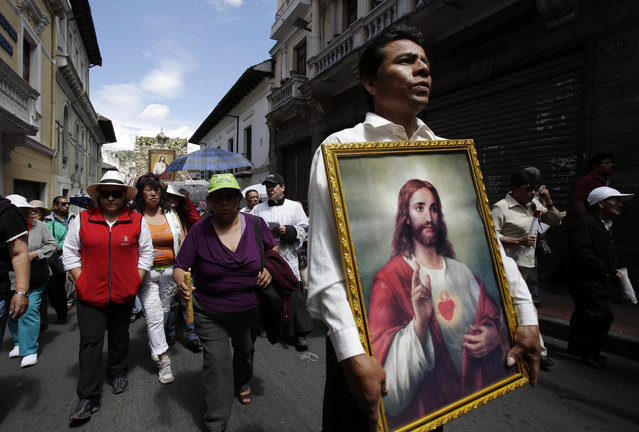 In this June 14, 2015 photo, a man parades with a framed image of the Sacred Heart of Jesus during a procession marking Ecuador's identity as a Catholic nation with its consecration to the Sacred Heart of Jesus in 1874, in Quito. (Photo by Dolores Ochoa/AP Photo)