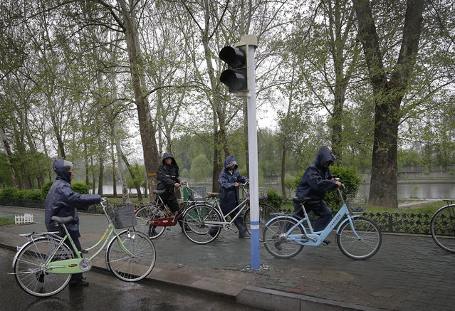 North Koreans push their bicycles in the rain on a pathway along the Pothong River at the end of a work day on Thursday, May 5, 2016, in Pyongyang, North Korea. (Photo by Wong Maye-E/AP Photo)