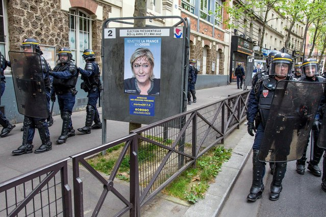 French police forces march next to a Marine Le Pen's campaign poster during a protest against far-right Front National (FN) party in Paris, France, 16 April 2017. The demonstration was organised by leftist associations against Front National candidate Marine Le Pen and her political meeting held in Paris on 17 April 2017. France holds the first round of the 2017 presidential elections on 23 April 2017. (Photo by Christophe Petit Tesson/EPA)