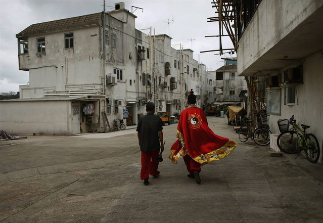 A Taoist priest walks with a musician to attend a ritual to honor the dead at Hong Kong's Cheung Chau island May 5, 2014, one day before the Bun Festival. The festival celebrates the islanders' deliverance from famine many centuries ago and is meant to placate ghosts and restless spirits. (Photo by Bobby Yip/Reuters)