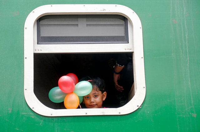 A child holding balloons looks out from the window of a train as people travel to their home villages to celebrate Eid-al-Adha, at the Kamlapur Railway Station in Dhaka, Bangladesh, 09 August 2019. Eid al-Adha is the holiest of the two Muslims holidays celebrated each year, it marks the yearly Muslim pilgrimage (Hajj) to visit Mecca, the holiest place in Islam. Muslims slaughter a sacrificial animal and split the meat into three parts, one for the family, one for friends and relatives, and one for the poor and needy. (Photo by Monirul Alam/EPA/EFE)