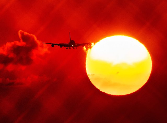 An aircraft passes the rising sun as it approaches the airport in Frankfurt, Germany, Wednesday, August 21, 2019. (Photo by Michael Probst/AP Photo)