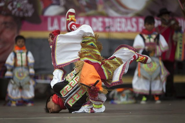 "A young ""scissors"" dancer performs in a national scissors dance competition at Lima's Exposition Park, May 18, 2014. The Danza de las tijeras, or scissors dance, is a traditional dance from the Peruvian southern region of the Andes, in which two or more performers take turns dancing while accompanied with music from a harp and a violin. Dancers would display various skills and moves, which include cutting the air with the use of a scissors. (Photo by Enrique Castro-Mendivil/Reuters)"