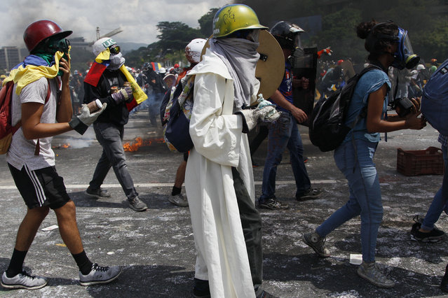 Anti-government protesters hold bags and glass bottles of fecal matter to throw at Bolivarian National Guards during an opposition march in Caracas, Venezuela, Wednesday, May 10, 2017. (Photo by Ariana Cubillos/AP Photo)