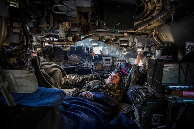 A Ukrainian government soldier rests inside an armored personnel carrier at a checkpoint near Slovyansk, Ukraine, Wednesday, May 21, 2014. The government has over the past week had its hand in the east strengthened by a sequence of strongly worded statements by metals tycoon Rinat Akhmetov, who owns major industrial assets in Donetsk region. (Photo by Petr Shelomovskiy/AP Photo)