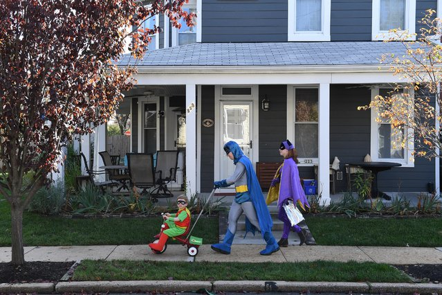 Dressed as Batman, Jacob Crowe pushes his son, Alex Crowe, 4, dressed as Robin as his wife, Alison Lesht, dressed as Batgirl follows behind after they attended the annual Del Ray Halloween Parade, in Alexandria, Va. on October 27, 2019. (Photo by Matt McClain/The Washington Post)