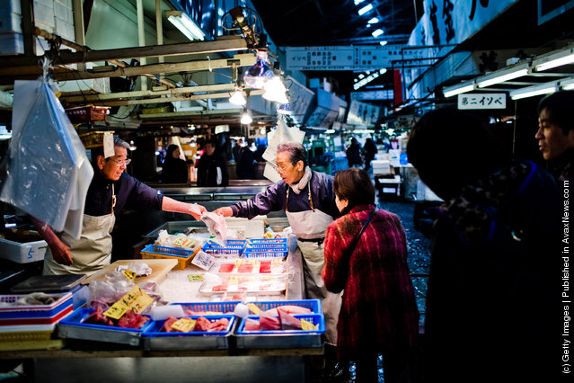 Workers point to a fish as they serve a customer at the Tsukiji fish market