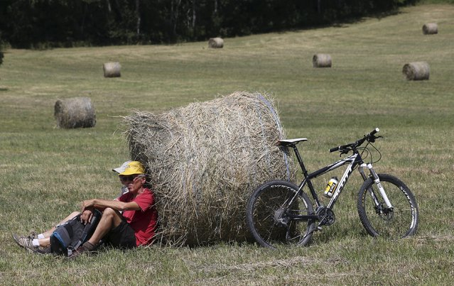 A couple waits for the pack of riders during the 18th stage of the 102nd Tour de France cycling race from Gap to Saint-Jean-de-Maurienne in the French Alps July 23, 2015. (Photo by Stefano Rellandini/Reuters)