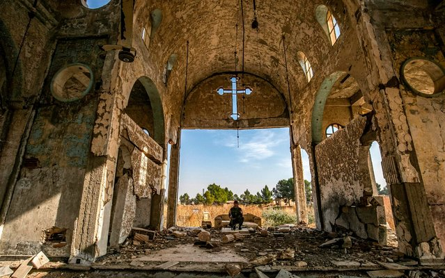 A member of the Khabour Guards (MNK) Assyrian Syrian militia, affiliated with the Syrian Democratic Forces (SDF), sits in the ruins of the Assyrian Church of the Virgin Mary, which was previously destroyed by Islamic State (IS) group fighters, in the village of Tal Nasri south of the town of Tal Tamr in Syria's northeastern Hasakah province on November 15, 2019. The few Assyrian Christians who escaped the Islamic State group invasion in 2015, and did not choose to emigrate, now anxiously watch the advance of Turkish forces toward their villages in southern Hassakeh province. (Photo by Delil Souleiman/AFP Photo)