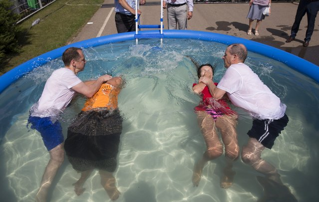 Jehovah's Witnesses are baptized in a pool during a regional congress of Jehovah's Witnesses at Traktar Stadium in Minsk, Belarus, July 25, 2015. (Photo by Vasily Fedosenko/Reuters)