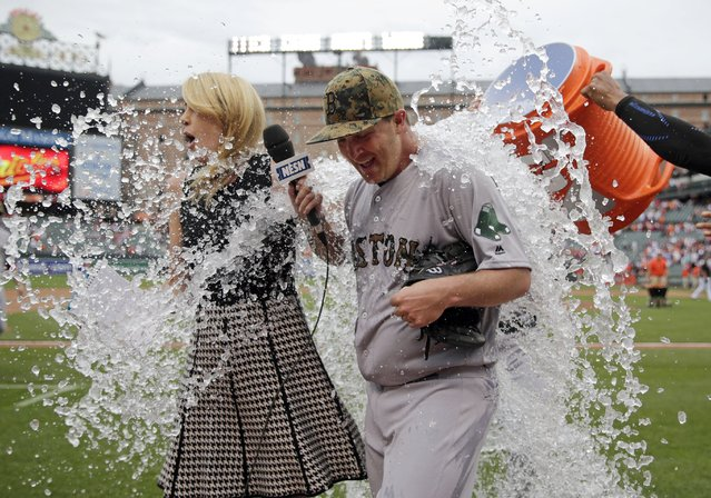 Boston Red Sox starting pitcher Steven Wright, right, is doused by teammates during a post-game television interview after closing out a baseball game against the Baltimore Orioles in Baltimore, Monday, May 30, 2016. Boston won 7-2. (Photo by Patrick Semansky/AP Photo)