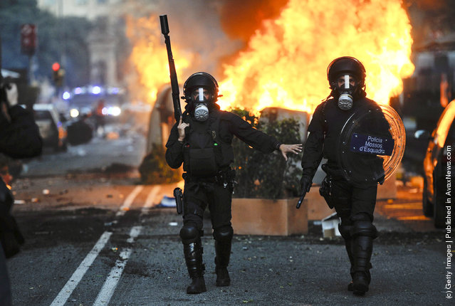 Riot police walk past burning garbage containers during heavy clashes with demonstrators during a 24-hour strike on March 29, 2012 in Barcelona, Spain