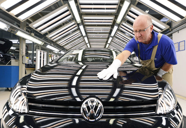 In this November 9, 2012 file photo worker Michael Keil checks a  Golf VII car during a press tour at the plant of the German car manufacturer Volkswagen AG (VW) in Zwickau, central Germany. Volkswagen AG says Wednesday, July 29, 2015, that profits slipped by 16 percent in the second quarter. (Photo by Jens Meyer/AP Photo)
