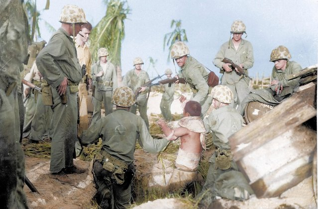Captured wounded Japanese soldier surrounded by Marines on Kwajalein Atoll, Marshall Islands. During World War II, it's estimated that between 19,500 and 50,000 members of the Imperial Japanese military surrendered to the Allies. (Photo by Royston Leonard/Mediadrumworld)