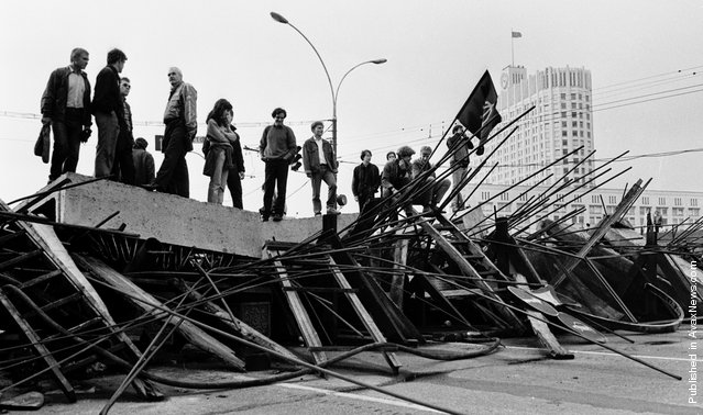 People stand on a barricade in front the Russian White House in Moscow on August 21, 1991