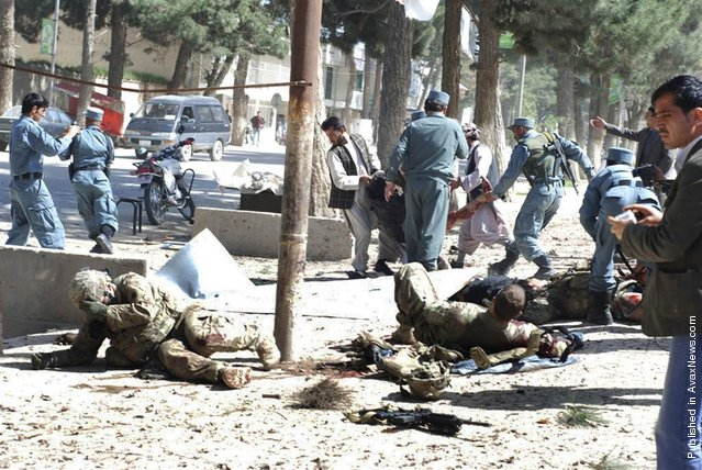 Wounded U.S. soldiers lie on the ground at the scene of a suicide attack in Maimanah, Afghanistan, on April 4, 2012. A suicide bomber blew himself up, killing at least 10 people, including three NATO service members