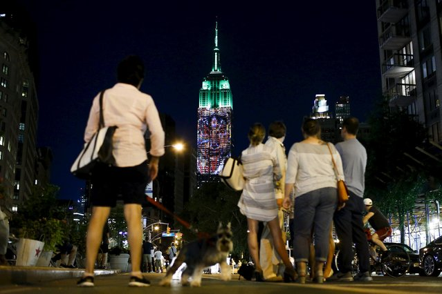 People watch as an image is projected onto the Empire State Building as part of an endangered species projection to raise awareness, in New York August 1, 2015. (Photo by Eduardo Munoz/Reuters)