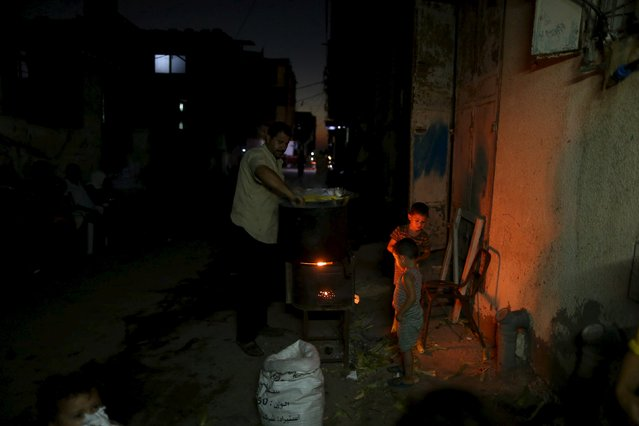 A Palestinian man sells corn during power cut at Shatti (beach) refugee camp in Gaza City July 23, 2015. (Photo by Mohammed Salem/Reuters)