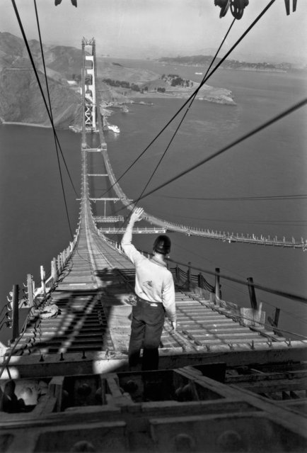 A construction worker stands at one end of the catwalks that span the Golden Gate between the two towers, San Francisco, California, December 1935. (Photo by Underwood Archives/Getty Images)