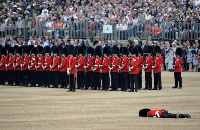 """A soldier collapses on Horse Guards Parade ahead of the Queen's Birthday Parade, """"Trooping the Colour"""", in London on June 11, 2016. Trooping The Colour and the fly-past are part of a weekend of events to celebrate the Queen's 90th birthday. (Photo by Oli Scarff/AFP Photo)"""