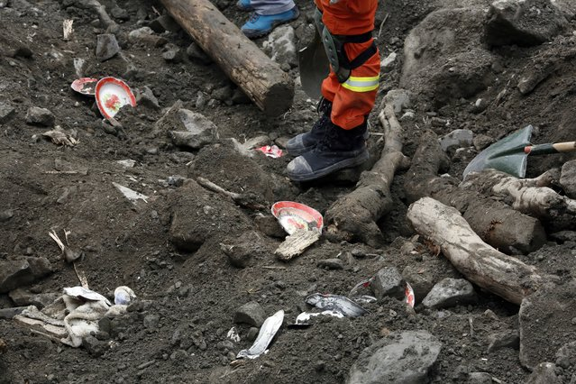 Household goods are scattered among the debris as rescue workers search for victims at the site of a landslide in Maoxian County in southwestern China's Sichuan Province, Sunday, June 25, 2017. Emergency crews are searching through the rubble for victims after a landslide Saturday buried a picturesque mountain village under tons of soil and rocks, with more than 100 people remained missing. (Photo by Ng Han Guan/AP Photo)