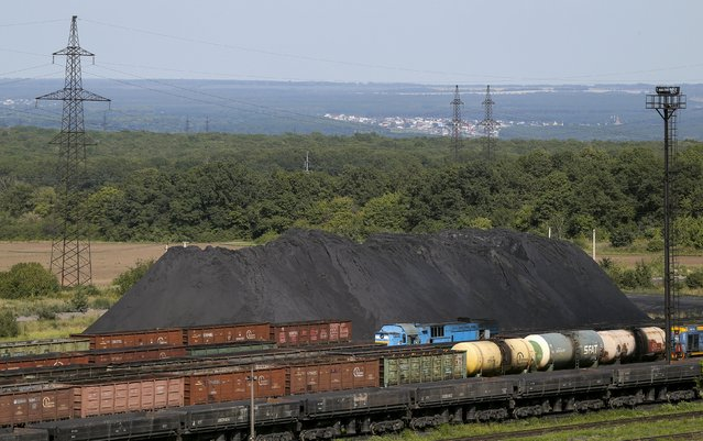 Cargo train carriages are seen in front an iron ore dump site of the Stoilensky mining and concentration plant (GOK), owned by the Novolipetsk (NLMK) steel mill, in the city of Stary Oskol in Belgorod region, Russia, August 4, 2015. (Photo by Maxim Shemetov/Reuters)