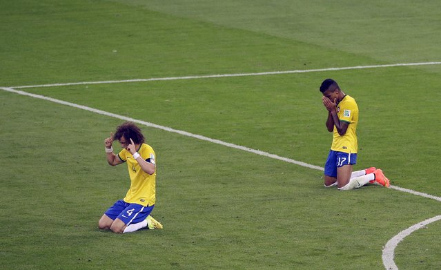 Brazil's David Luiz and Brazil's Luiz Gustavo fall to their knees at the end of the World Cup semifinal soccer match between Brazil and Germany at the Mineirao Stadium in Belo Horizonte, Brazil, Tuesday, July 8, 2014. Germany won 7-1. (Photo by Hassan Ammar/AP Photo)