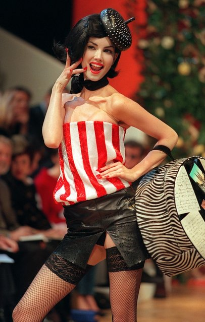 A model wears a red and white striped bustier over a black leather mini-skirt and fishnet stockings by British designer Alexander McQueen for the Givenchy 1999 Spring/Summer haute couture collection in Paris 17 January, 1999. (Photo by Eric Feferberg/AFP Photo)