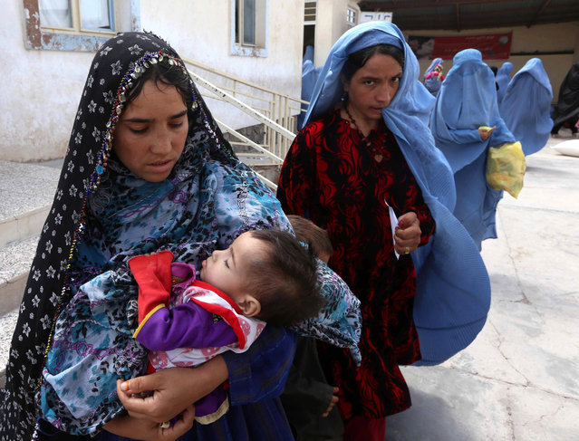 Afghan women wait to get medical treatment at the refugee camp in Herat, Afghanistan, 03 August 2015. The camp provides refugees with basic medical treatment, education, food and hygiene. (Photo by Jalil Rezayee/EPA)