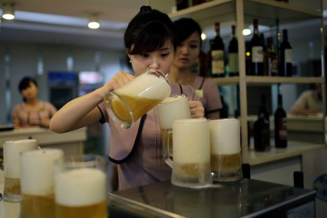 In this Wednesday, July 26, 2017, photo, a waitress pours a new type of Taedonggang beer, the eighth in its line of specialty brews, made of wheat and hops at the Taedonggang Brewery in Pyongyang, North Korea. Taedonggang beers are generally reputed to be world-class, which is a matter of national pride among many North Koreans. (Photo by Wong Maye-E/AP Photo)
