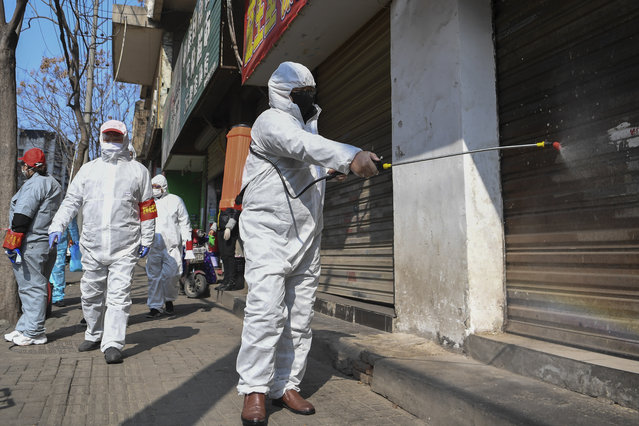 In this photo released by Xinhua News Agency, workers disinfect closed shop lots following the coronavirus outbreak, in Jiang'an District of Wuhan in central China's Hubei Province, Monday, February 10, 2020. Mainland China has reported another rise in cases of the new virus after a sharp decline the previous day, while the number of deaths grow over 900, with at least two more outside the country. (Photo by Cheng Min/Xinhua via AP Photo)