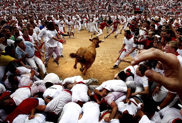 A cow jumps over revelers in a bullring during the second running of the bulls at the San Fermin fiestas in Pamplona, Spain on July 8, 2012