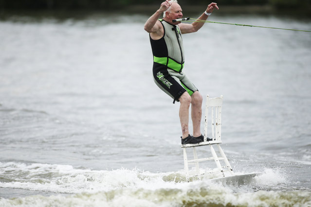 Carl Wolters stands on a chair while being pulled by a boat on the water. The Grand City Skiers water ski show was held as part of the Coast Guard Festival at Waterfront Stadium in downtown Grand Haven on Tuesday, July 29, 2014. (Photo by Tommy Martino/AP Photo/Muskegon Chronicle)