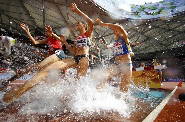Athletes jump a water obstacle in the women's 3000 metres steeplechase final during the 15th IAAF World Championships at the National Stadium in Beijing, China August 24, 2015. (Photo by Kai Pfaffenbach/Reuters)