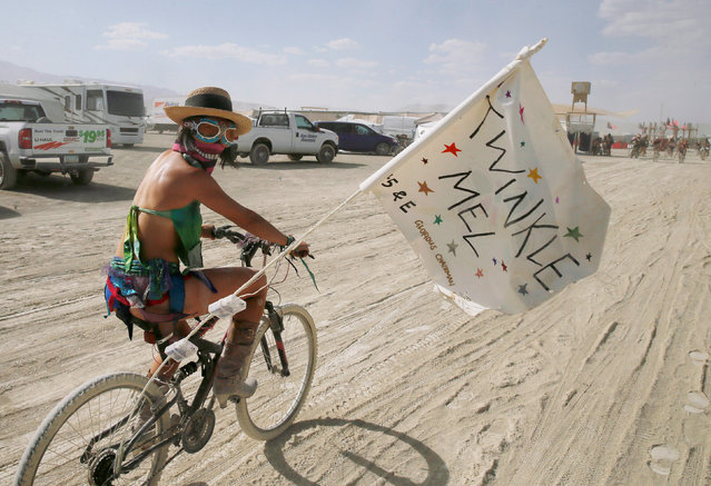 "A Burning Man participant who goes by the playa name ""Twinkle Mel"" bicycles through Black Rock City at Burning Man in the Black Rock Desert of Nevada, U.S. August 29, 2017. (Photo by Jim Urquhart/Reuters)"