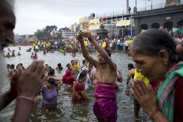 Indian devotees perform rituals in Godavari River during Kumbh Mela, or Pitcher Festival, in Nasik, India, Wednesday, August 26, 2015. (Photo by Tsering Topgyal/AP Photo)