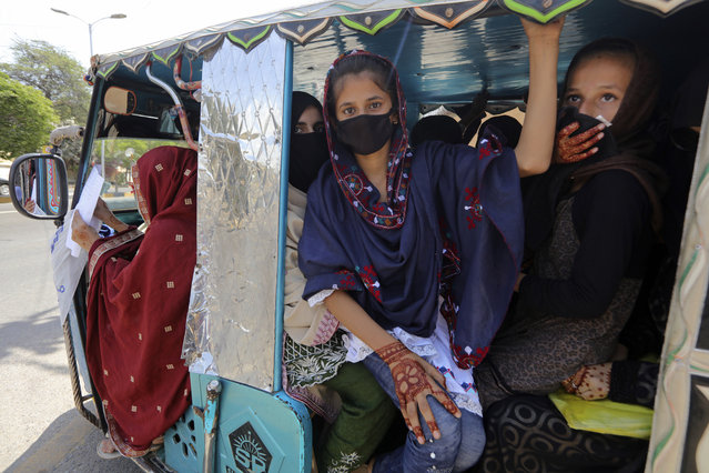People traveling in a motorized rickshaw wear face masks in an effort to avoid the spread of the coronavirus, in Karachi, Pakistan, Tuesday, March 24, 2020. Pakistani authorities said they'd shut down train operations across the country from Wednesday until March 31 in an effort to contain the spread of the virus. (Photo by Fareed Khan/AP Photo)
