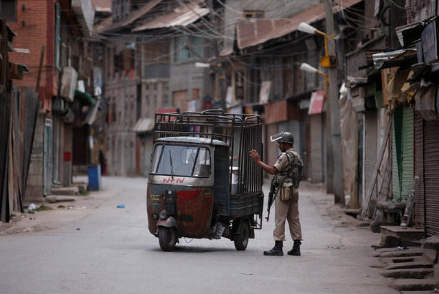 An Indian policeman stops an auto-rickshaw during a curfew in Srinagar, July 17, 2016. (Photo by Danish Ismail/Reuters)