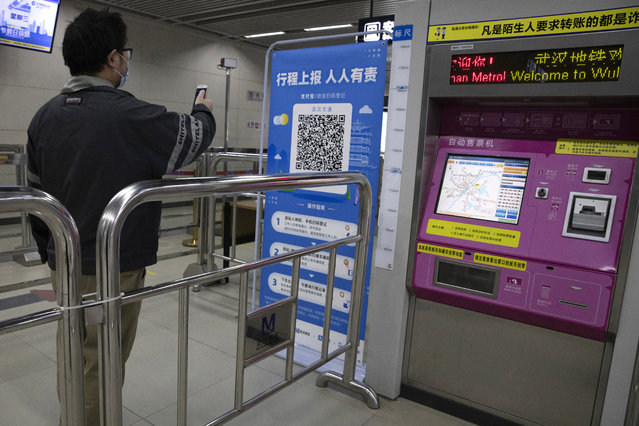 """In this April 1, 2020 photo, a passenger scans a QR code to get his green pass at a subway station in Wuhan in central China's Hubei province. Life in China post-coronavirus outbreak is ruled by a green symbol on a smartphone screen. Green signifies the """"health code"""" that says the user is symptom-free. It is required to board a subway, check into a hotel or enter Wuhan, the city where the global pandemic began. (Photo by Ng Han Guan/AP Photo)"""