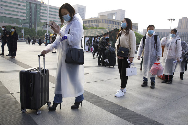 Passengers wearing face masks and rain coats to protect against the spread of new coronavirus gather outside of Hankou train station after of the resumption of train services in Wuhan in central China's Hubei Province, Wednesday, April 8, 2020. After 11 weeks of lockdown, the first train departed Wednesday morning from a re-opened Wuhan, the origin point for the coronavirus pandemic, as residents once again were allowed to travel in and out of the sprawling central Chinese city. (Photo by Ng Han Guan/AP Photo)