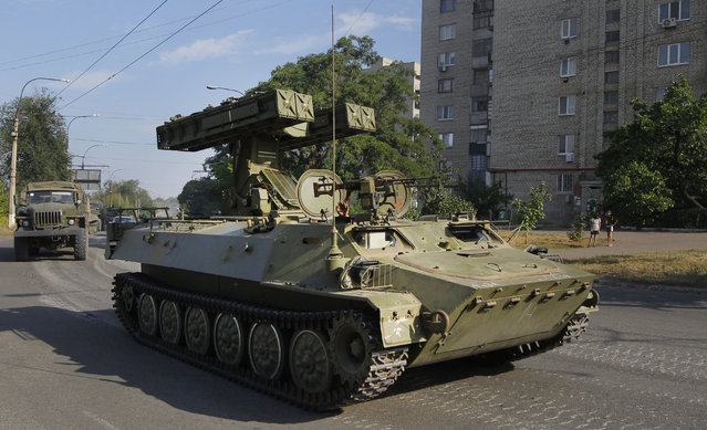This is a Sunday, August 17, 2014  file photo of a pro-Russian missile launcher as it drives in the town of Krasnodon. A column of several dozen heavy vehicles, including tanks and at least one rocket launcher, rolling through rebel-held territory on August 17. AP reporters say convoys of military weaponry and supplies have been coming from the direction of Russia into rebel-held Ukraine. (Photo by Sergei Grits/AP Photo)