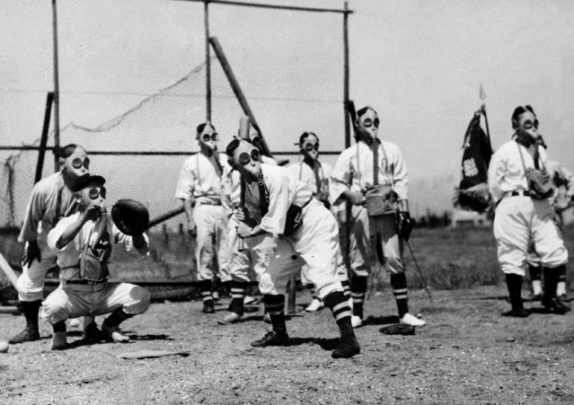 Ball players are seen playing while wearing gas masks, September 3, 1938 in a psychological and physiological experiment by the Tokyo air defense bureau. (Photo by AP Photo)