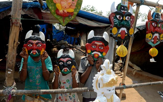 Children of a vendor pose with demon-masks to be hung outside homes believed to ward off negative energy during a government-imposed nationwide lockdown as a preventive measure against the COVID-19 coronavirus, at a roadside stall in Hyderabad, on April 18, 2020. (Photo by Noah Seelam/AFP Photo)