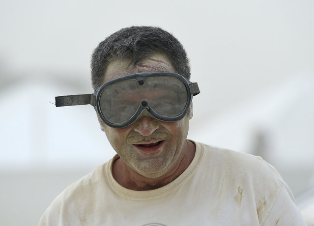 Geroge Krieger stands outside while securing his tent during a morning dust storm at Burning Man on the Black Rock Desert in Gerlack, Nev. on Saturday, August 29, 2015. (Photo by Andy Barron/The Reno Gazette-Journal via AP Photo)
